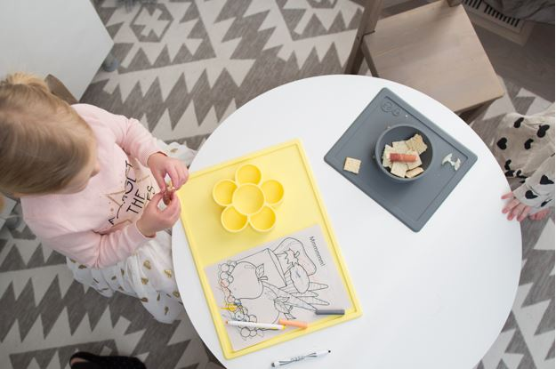 We are looking overheat as one child sits at a small kid's table coloring a picture on a piece of paper with markers her silicone EZPZ Play Mat. Also at the table is a silicone EZPZ Happy Bowl mat full of a snack which a second child is enjoying though we only see part of their hand.