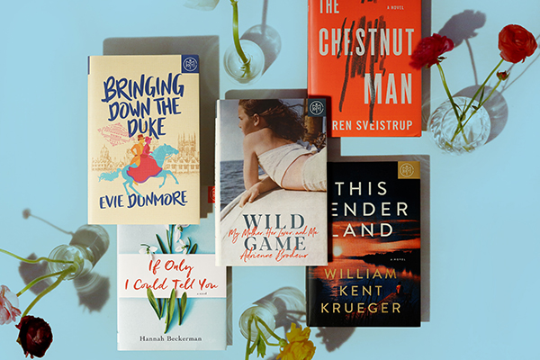 five books on a blue background next to flowers in glass vases