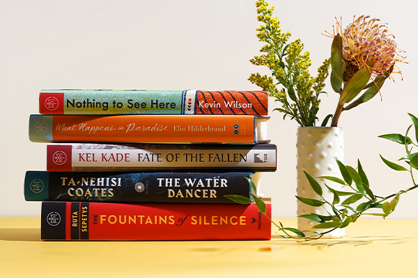 a stack of books on a table next to a white vase with flowers in it