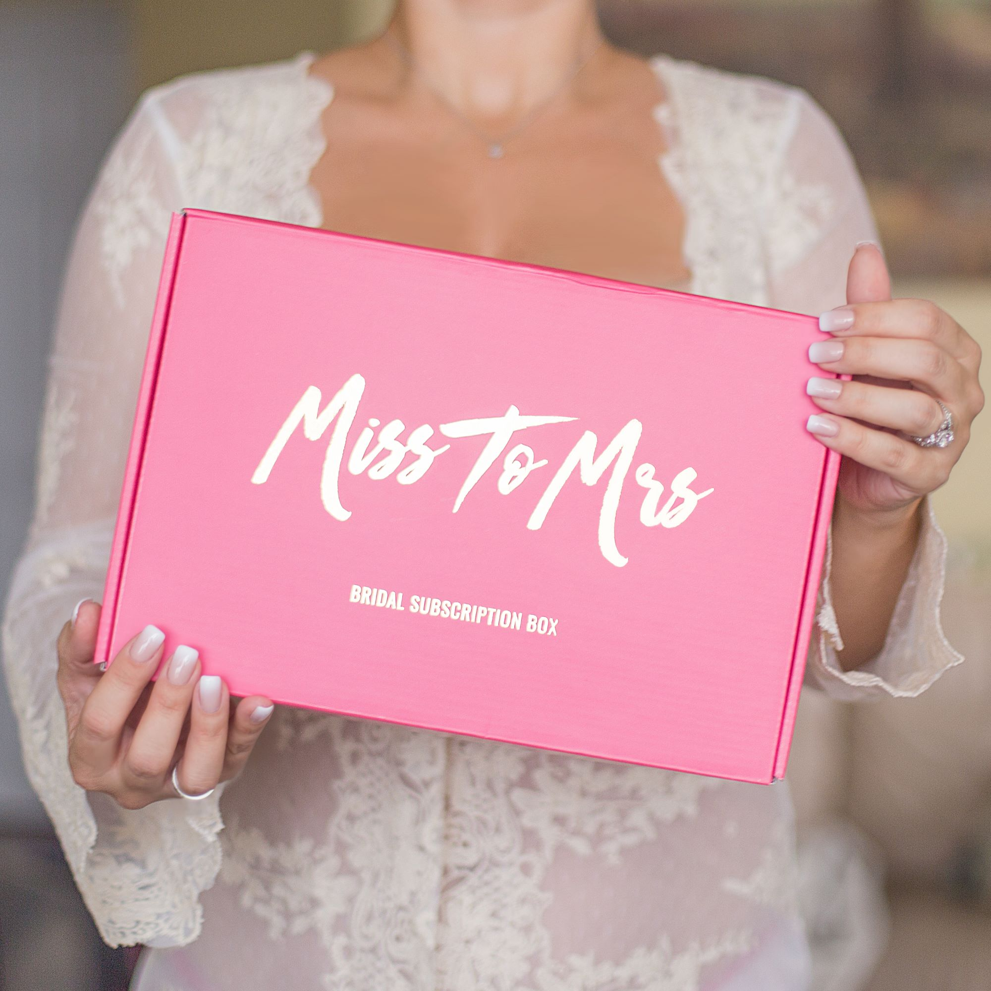 Girl holding a pink Miss to Mrs Bridal Subscription Box