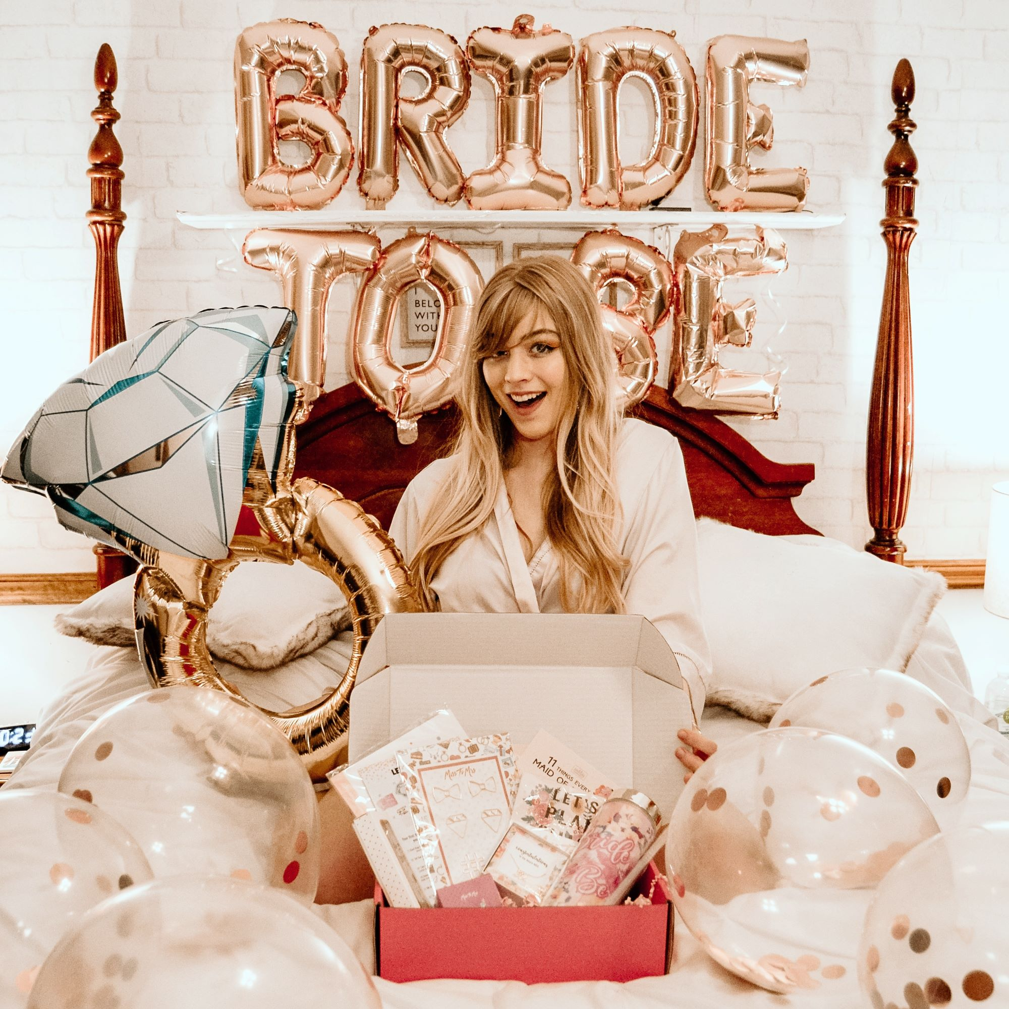 Happy bride-to-be with Miss to Mrs subscription box full of bridal must-haves