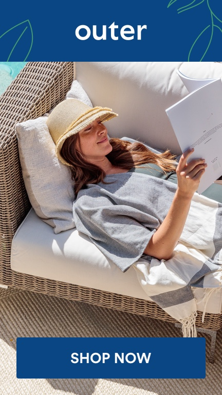 woman lounging on Outer sofa and reading by the pool