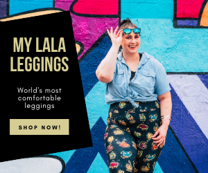 plus size model in zodiac leggings smiling with hand on glasses