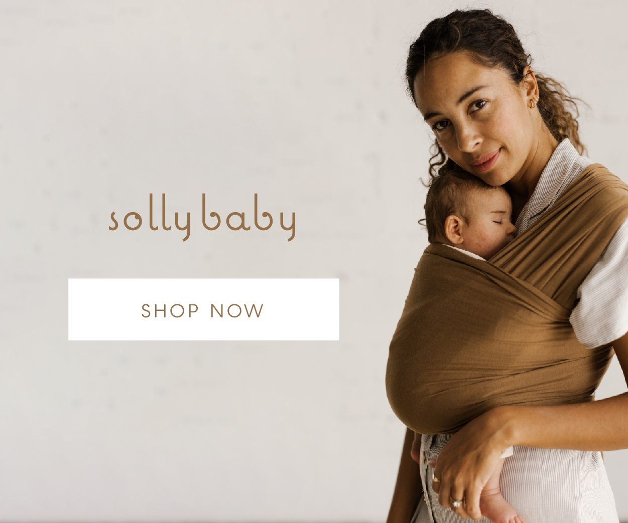 Mom bonding with her baby while wearing a pink Solly Baby Wrap.